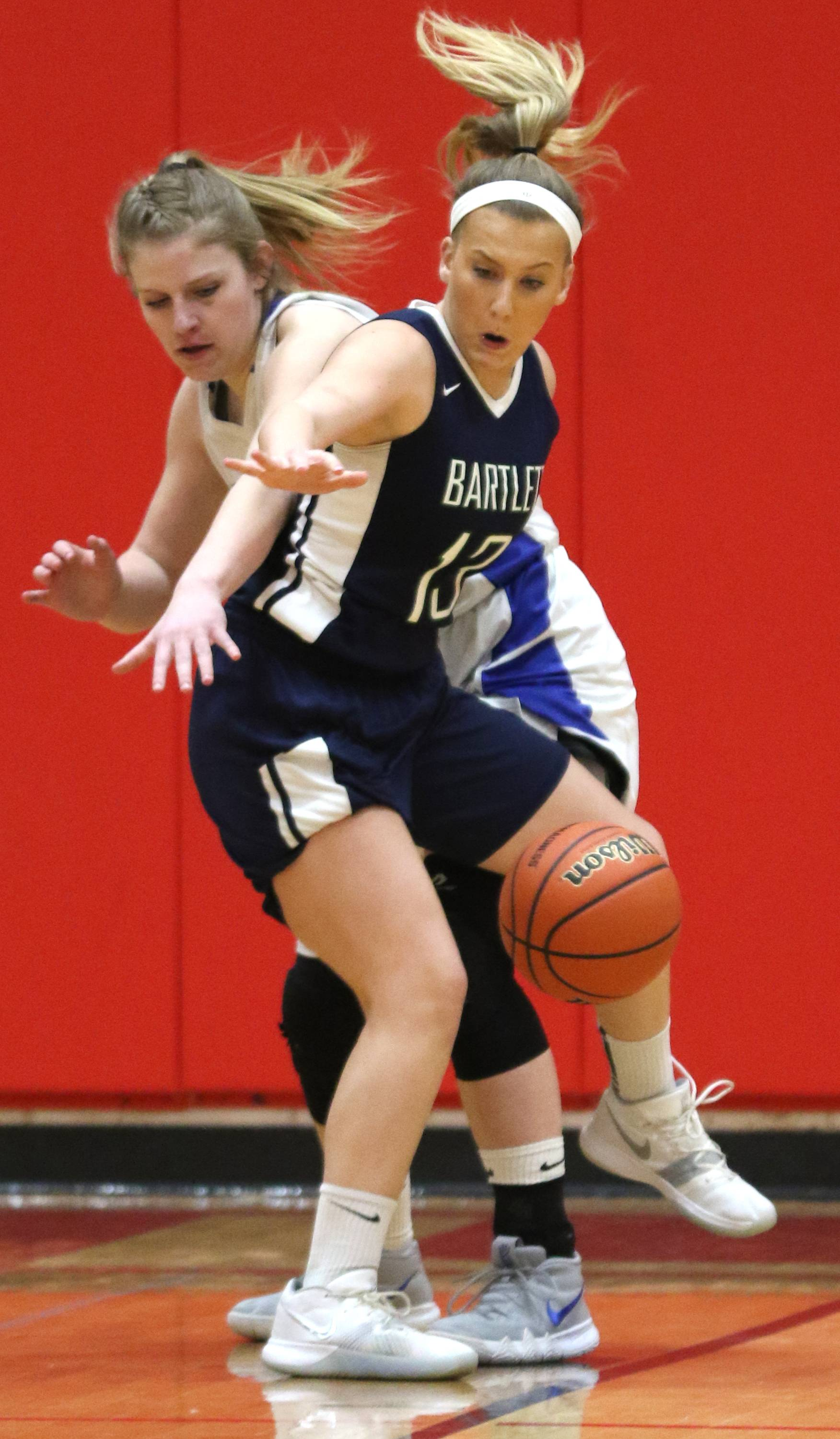 Bartlett's Teagan Noesen, front, and Geneva's Lindsay Blackmore scramble for the ball during sectional semifinal girls basketball action at Batavia Monday night.