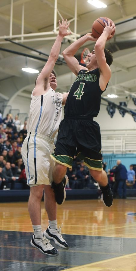 Fremd's Dean Ganas drives to the basket against Prospect's TJ Johannesen during the Mid-Suburban League boys basketball championship game in Mount Prospect Wednesday. Fremd won the game 75-72.