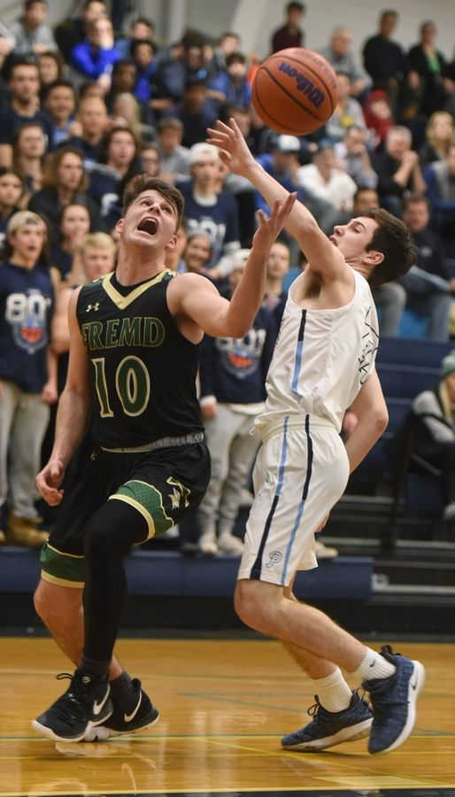 Fremd's Jake Schoffstall, left, tries to grab the ball after drawing contact from Prospect's Jack Schneider during the Mid-Suburban League boys basketball championship game in Mount Prospect Wednesday. Fremd won the game 75-72 in double overtime.