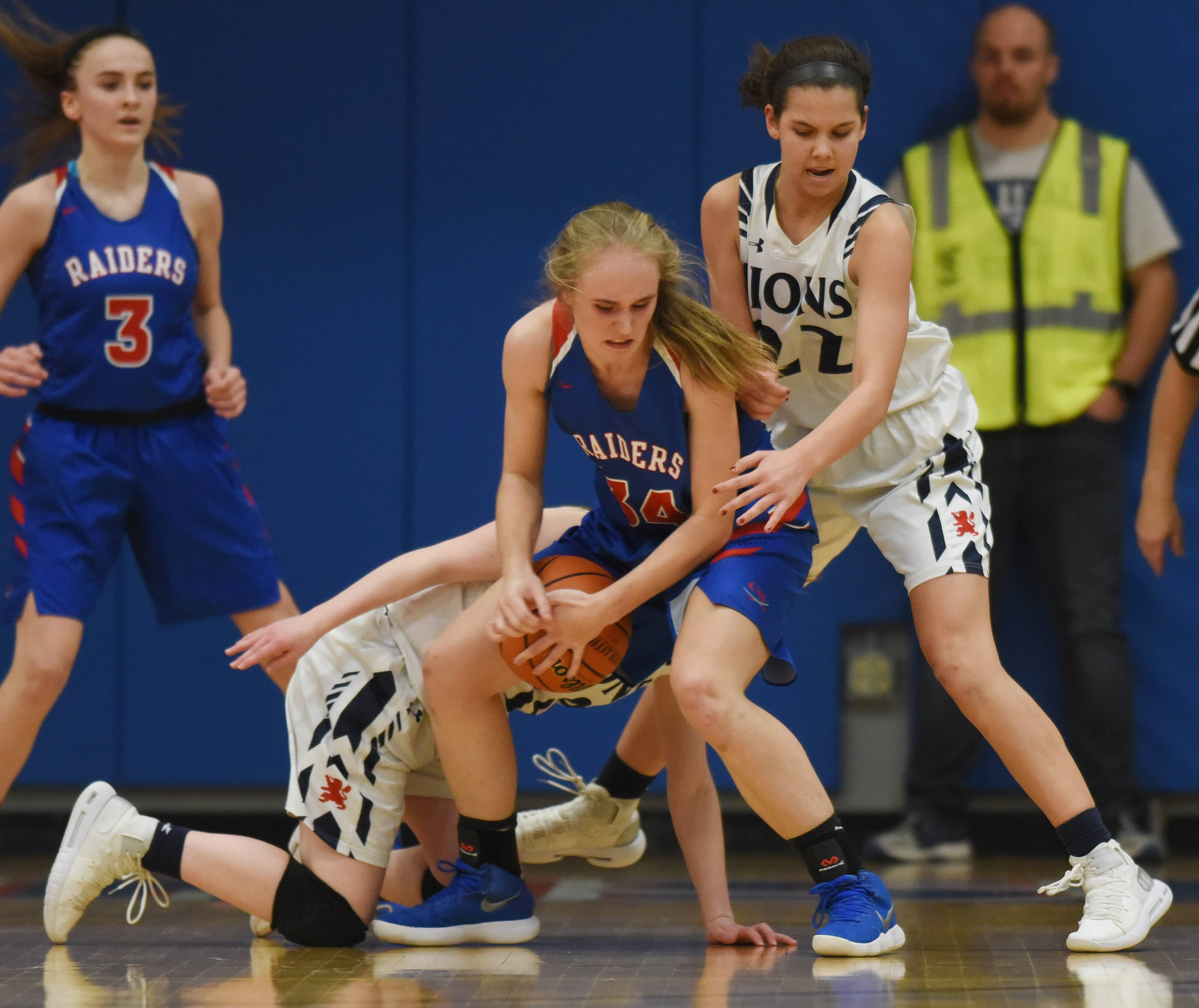 Glenbard South's Alex Wilharm, middle, comes up with the ball between St. Viator's Emma Morrisey, back, and Joy Bergstrom, right, during the Class 3A girls baskeball supersectional at Elgin Community College Monday.