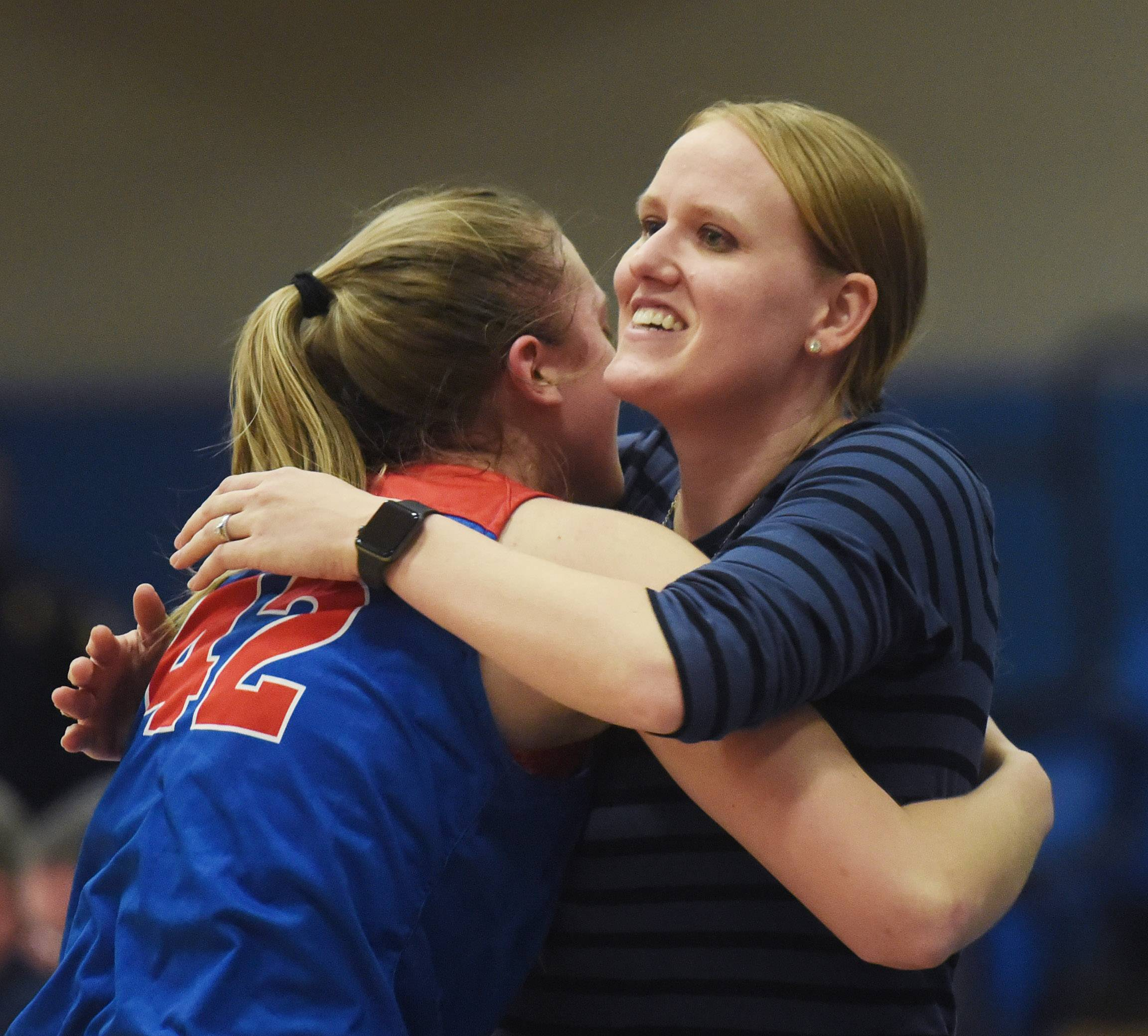 Glenbard South's Maggie Bair gets a hug from coach Morgan Eufrasio at the conclusion of the Raider's 34-24 victory over St. Viator during the Class 3A girls baskeball supersectional at Elgin Community College Monday.
