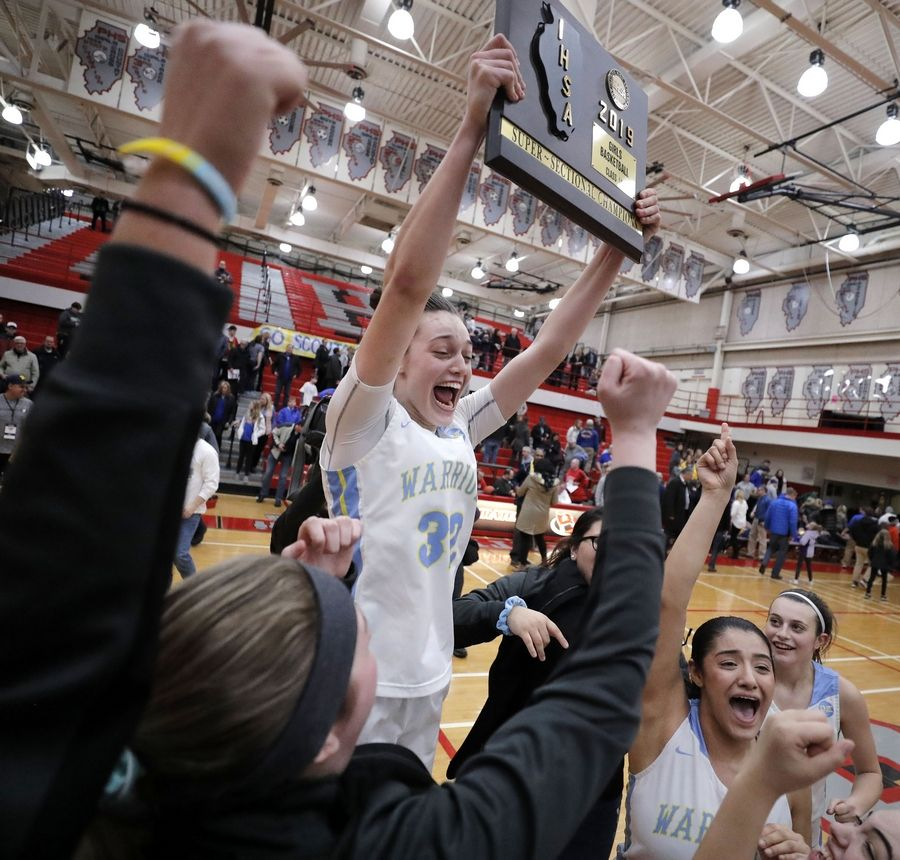 Maine West's Angela Dugalic hoists the supersectional trophy after beating Lake Forest Monday night at Palatine High School.
