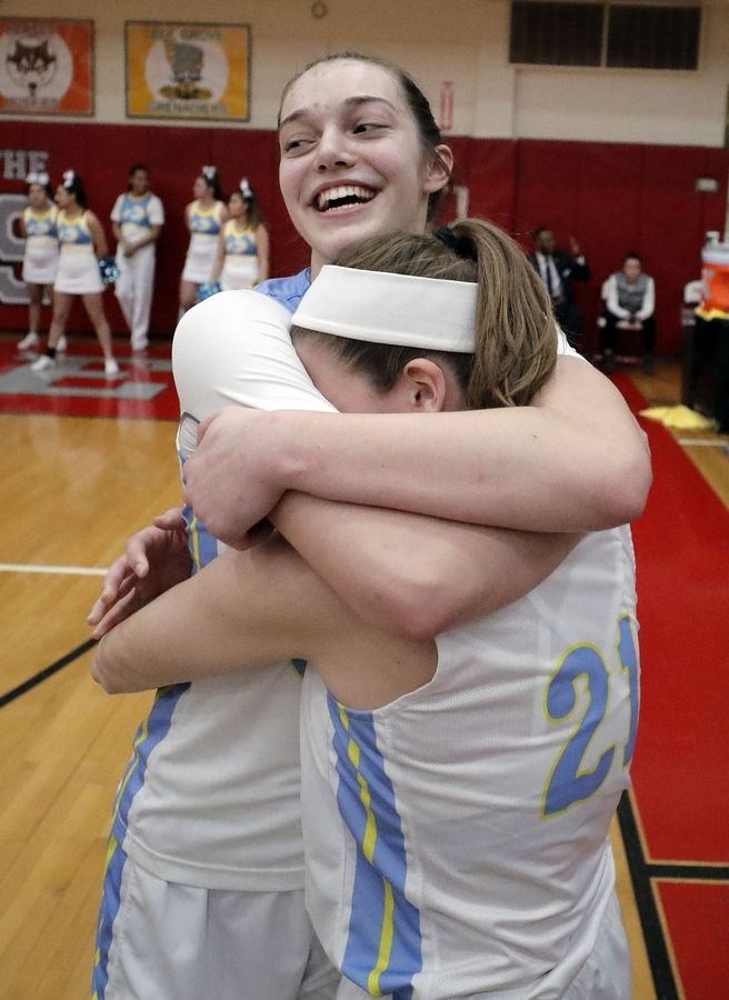 Maine West's Angela Dugalic hugs Ellie Centella after beating Lake Forest in the supersectional Monday night at Palatine High School.