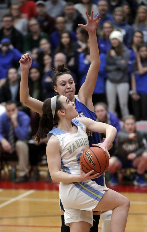 Maine West's Dylan Van Fleet, bottom drives on Lake Forest's Halle Douglass during their supersectional game Monday night at Palatine High School.