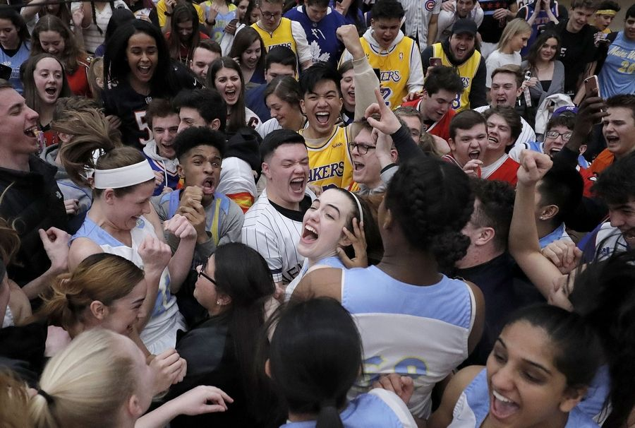 Maine West fans mob the players after beating Lake Forest in the supersectional Monday night at Palatine High School.
