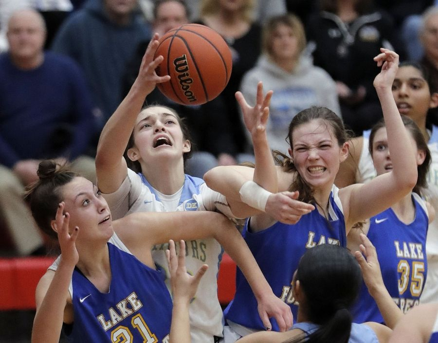 Maine West's Angela Dugalic battles for a rebound with Lake Forest's Halle Douglass, left, and Grace Tirzmalis during their supersectional game Monday night at Palatine High School.