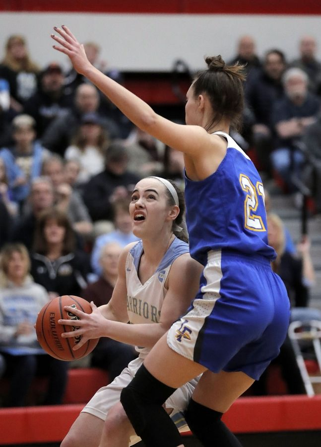 Maine West's Dylan Van Fleet, left, drives on Lake Forest's Halle Douglass during their supersectional game Monday night at Palatine High School.