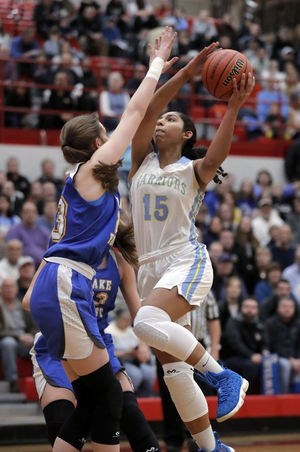 Maine West's Rachel Kent (15) drives on Lake Forest's Grace Tirzmalis during their supersectional game Monday night at Palatine High School.