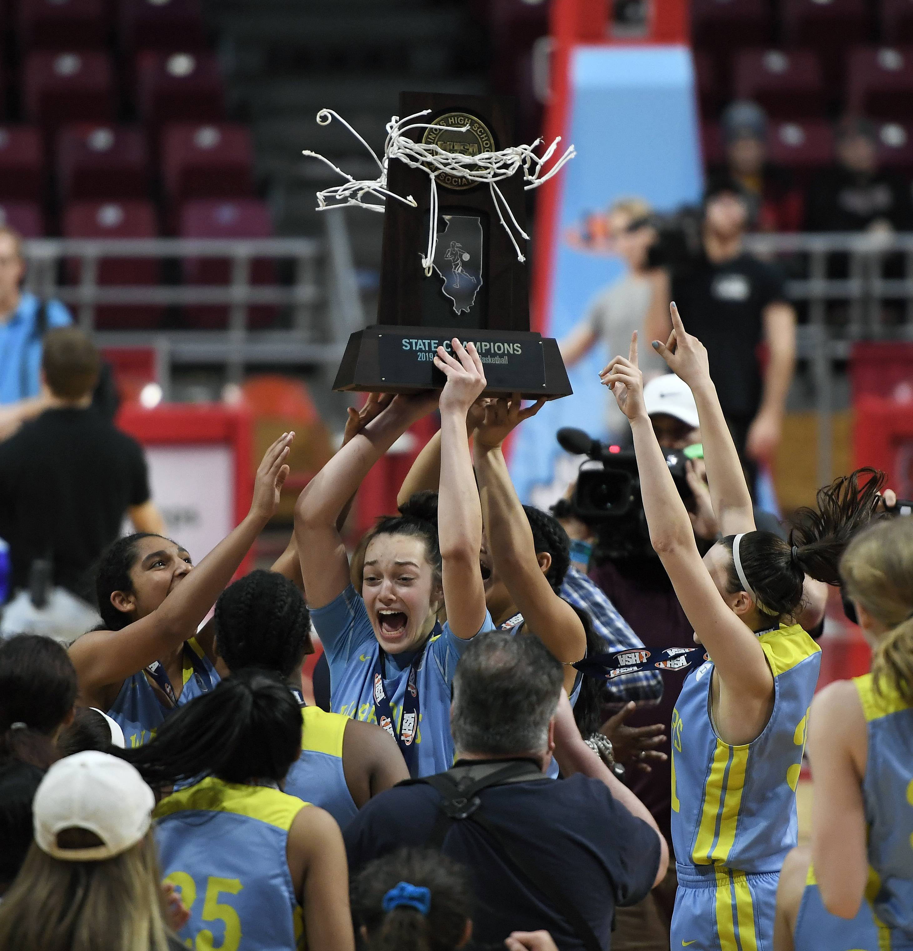 Maine West's Angela Dugalic holds up the Class 4A state championship trophy for the fans after the Warriors beat Mother McAuley 58-46 in the IHSA girls state basketball finals at Redbird Arena in Normal.