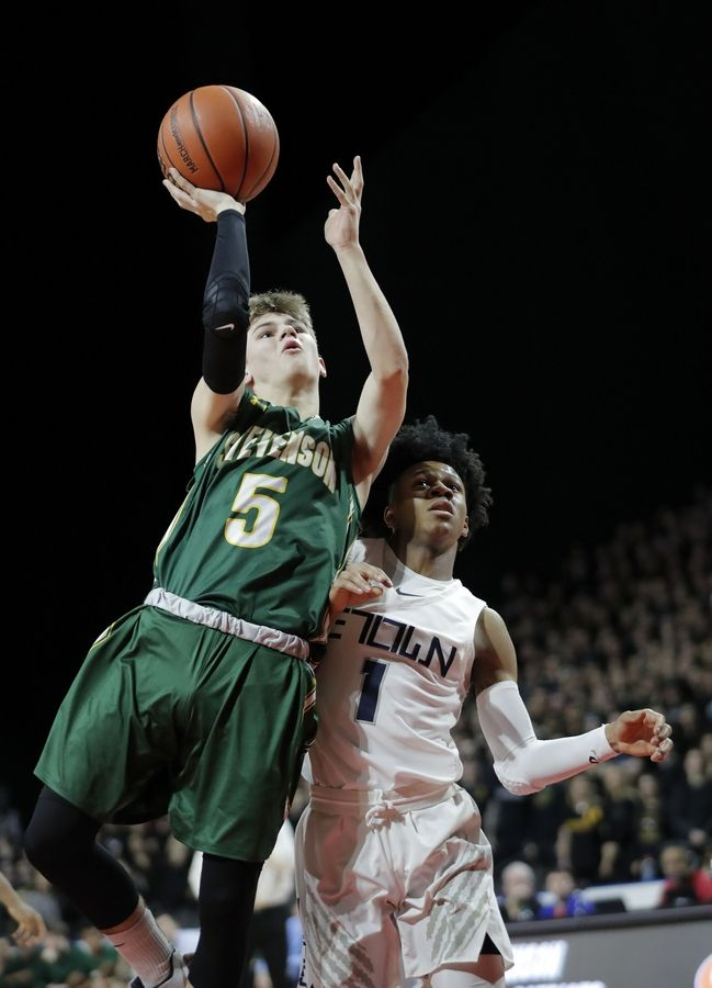 Stevenson's Evan Ambrose (5) shoots over Evanston's Jaheim Holden during the Class 4A boys basketball supersectional Tuesday night at the Sears Centre in Hoffman Estates.
