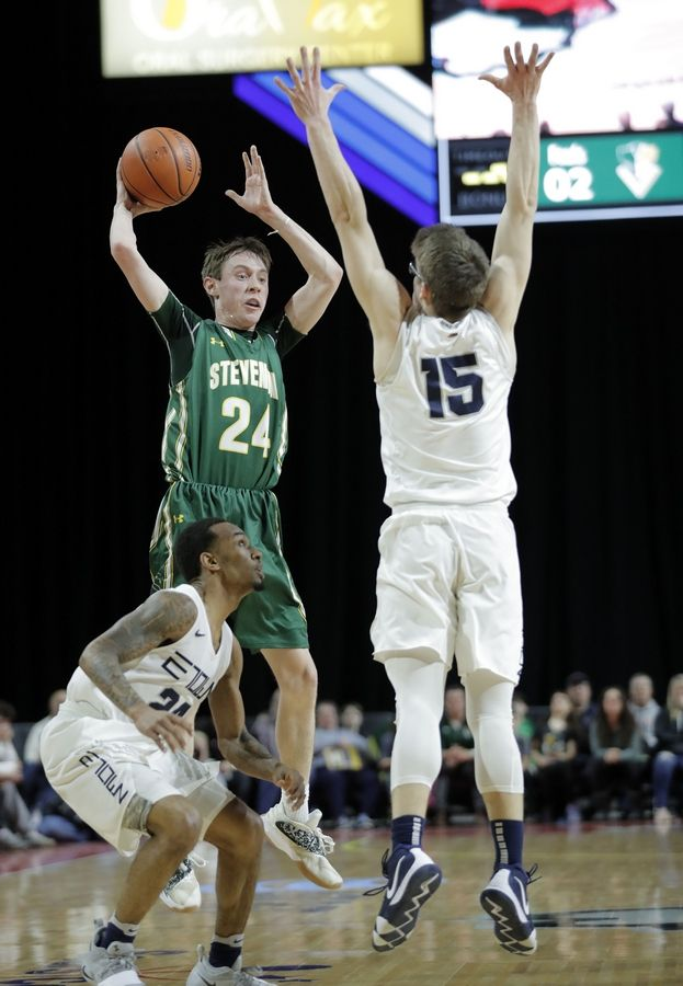 Stevenson's Matthew Ambrose (24) looks to pass around Evanston's Blake Peters during the Class 4A boys basketball supersectional Tuesday night at the Sears Centre in Hoffman Estates.