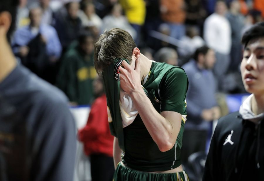 Stevenson's Matthew Ambrose covers his head after losing to Evanston in overtime during the Class 4A boys basketball supersectional Tuesday night at the Sears Centre in Hoffman Estates.