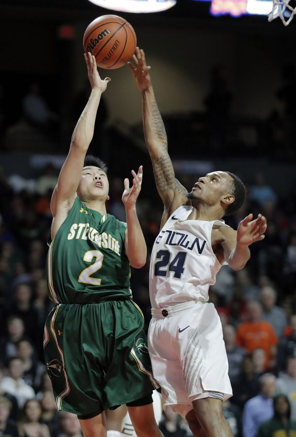 Stevenson's Luke Chieng, left, has his shot blocked by Evanston's Ryan Bost during the Class 4A boys basketball supersectional Tuesday night at the Sears Centre in Hoffman Estates.