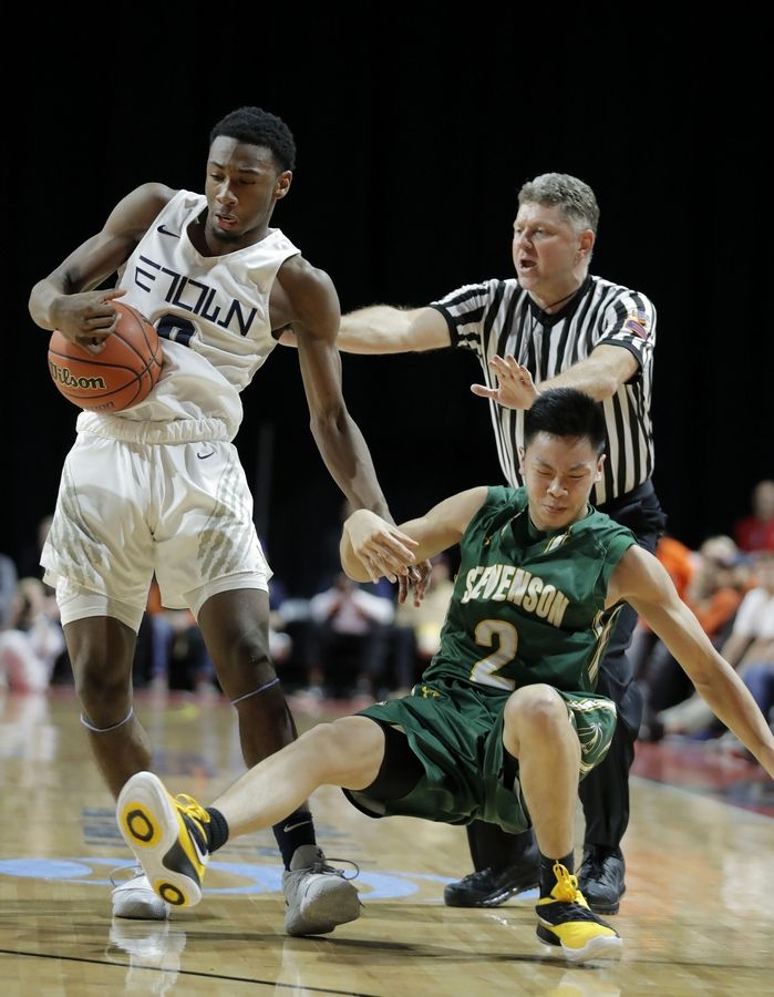 Stevenson's Luke Chieng, right, is thrown to the ground by Evanston's Jaylin Gibson during the Class 4A boys basketball supersectional Tuesday night at the Sears Centre in Hoffman Estates.