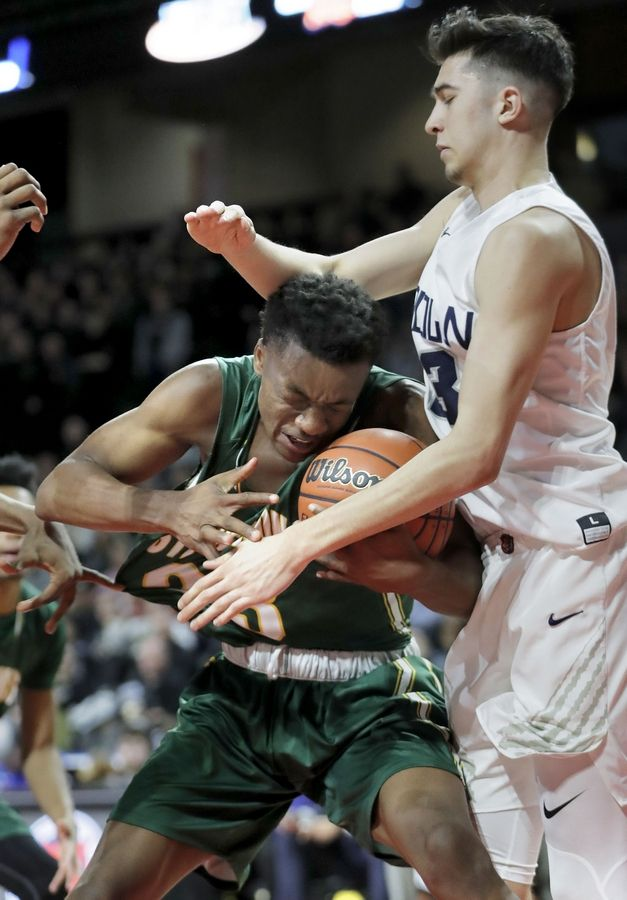 Stevenson's RJ Holmes, left, battles for a rebound with Evanston's Louis Lesmond during the Class 4A boys basketball supersectional Tuesday night at the Sears Centre in Hoffman Estates.