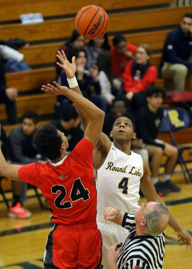 Grant's Tavarus Williams (24) and Round Lake's Hakim Williams tip off during action last season.