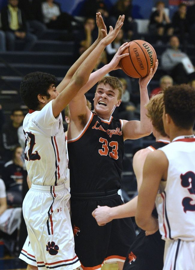 Libertyville's Jackson Watson (33) heads to the hoop under pressure from Conant's Rajat Mittal during action last season.
