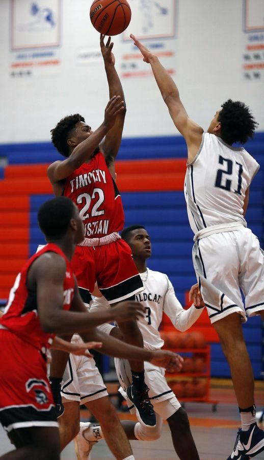 Timothy Christian's Matt Owens (22) puts up a shot over West Chicago's Christian Krahenbuhl (21) Friday during the 32nd Annual Chuck Mitchell Boys Basketball Tournament at Fenton High School in Bensenville.