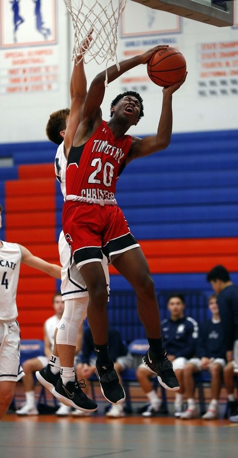 West Chicago's Daniel Roldan (22) tries to block a shot by Timothy Christian's Josh Harris (20) Friday during the 32nd Annual Chuck Mitchell Boys Basketball Tournament at Fenton High School in Bensenville.