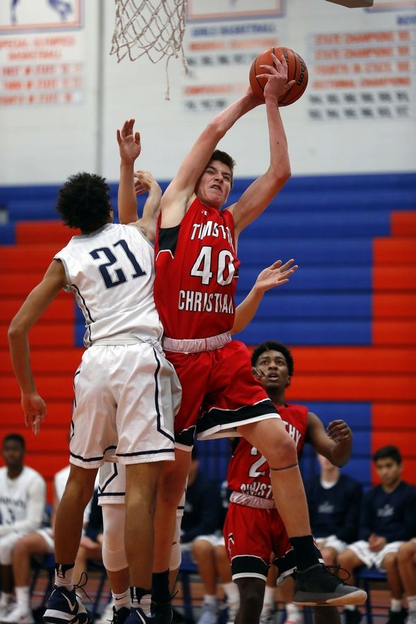 Timothy Christian's Ben VanderWal (40) goes to the hoop as West Chicago's Christian Krahenbuhl (21) tries to get the stop Friday during the 32nd Annual Chuck Mitchell Boys Basketball Tournament at Fenton High School in Bensenville.