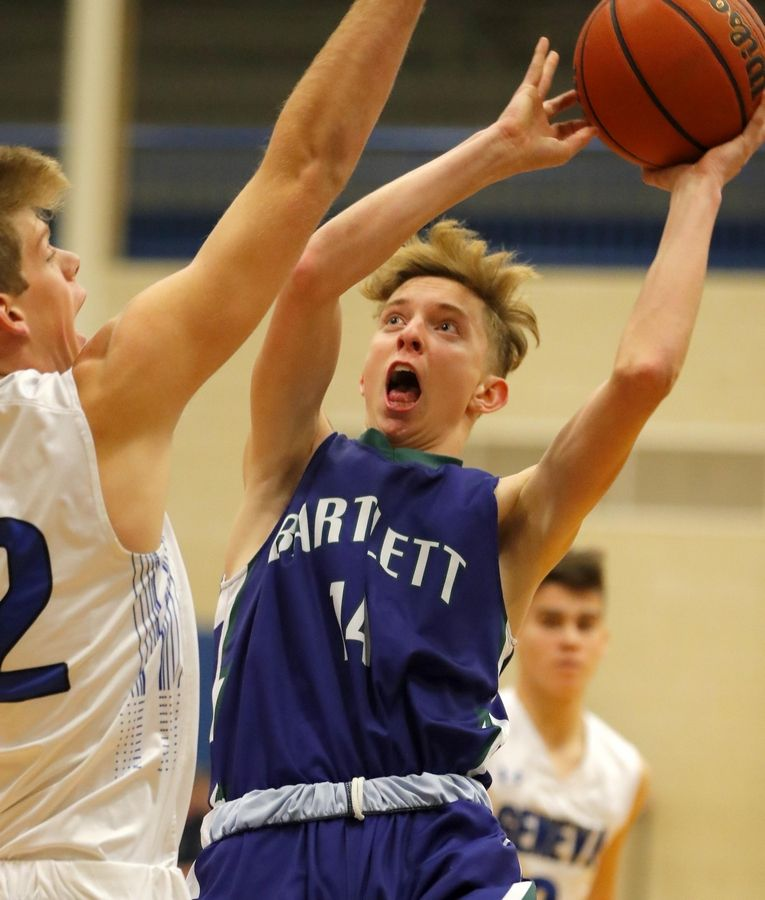 Bartlett's Hayden Angell takes a shot against the defense of Geneva's Dylan Fuzak in varsity boys basketball at Geneva Tuesday night.