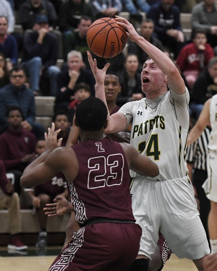 Stevenson's Matthew Ambrose battles for a loose ball with Zion-Benton's Kent Shepard in boys basketball at Stevenson on Friday.