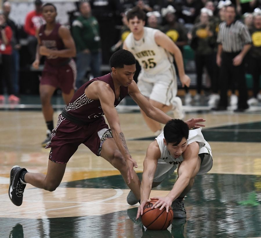 Stevenson's Andrew Chieng chases down a loose ball as Zion-Benton's Jahkai Ransom closes the gap in boys basketball at Stevenson on Friday.