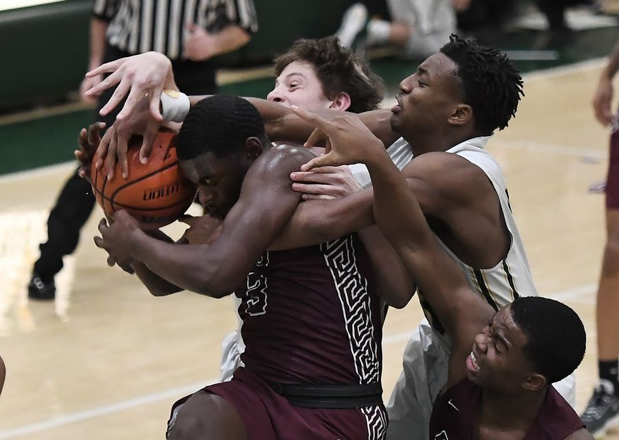 Zion-Benton's Floyd Bailey makes a grab for the rebound in a fight for possession as Stevenson applies pressure in boys basketball at Stevenson on Friday.