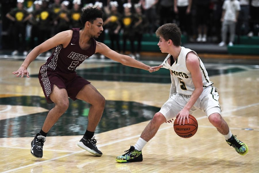Stevenson's Evan Ambrose does some fancy dribbling around Zion-Benton's Kayleb Naylor in boys basketball at Stevenson on Friday.