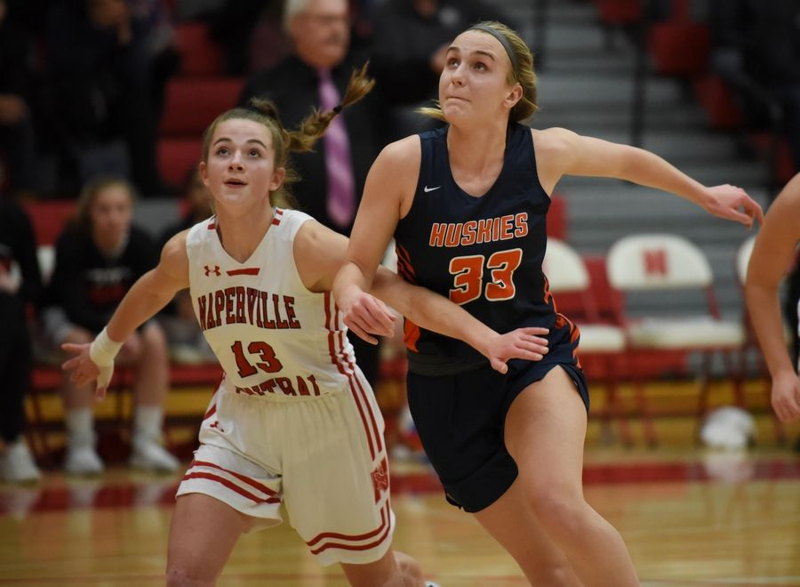 Naperville Central's Lauren Umbright and Naperville North's Greta Kampschroeder battle for position in a basketball game in Naperville Friday.