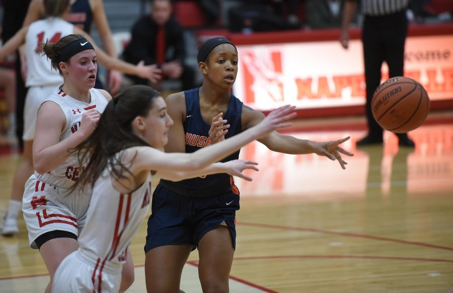Naperville North's Layla Henderson passes under pressure from Naperville Central's Gabriella Melby and Sara Opalka in a basketball game in Naperville Friday.