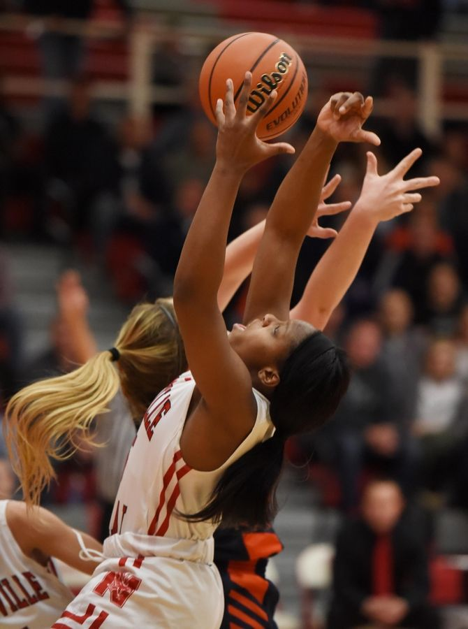 Naperville Central's Katlyn Allen fights for a rebound against Naperville North's Sarah Lockridge in a basketball game in Naperville Friday.