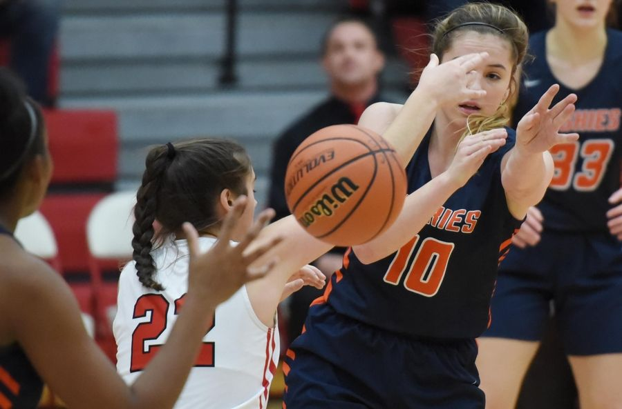 Naperville North's Sarah Lockridge passes under pressure from Naperville Central's Karly Maida in a basketball game in Naperville Friday.