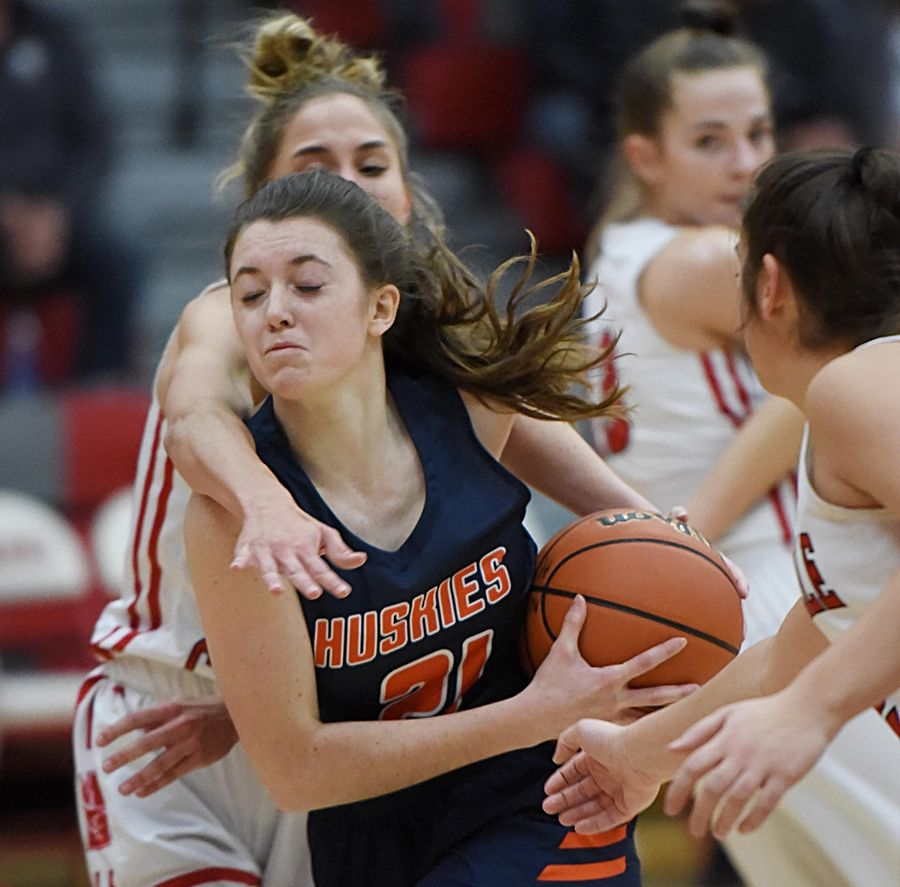 Naperville Central's Emily Spisak tries to stop Naperville North's Abby Drendel in a basketball game in Naperville Friday.