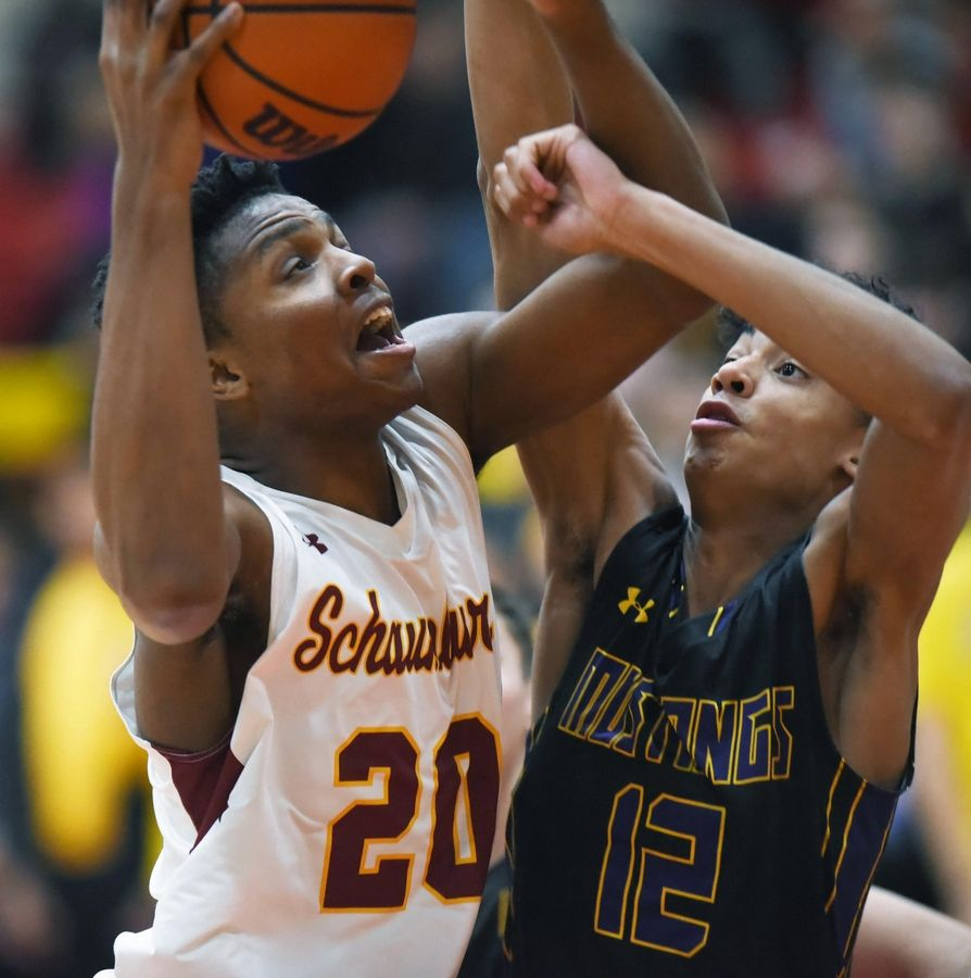 Schaumburg's Chris Hodges tries to score over Rolling Meadows' Max Christie earlier this season. The Saxons and Mustangs both play in the Jack Tosh Holiday Classic at York next week.