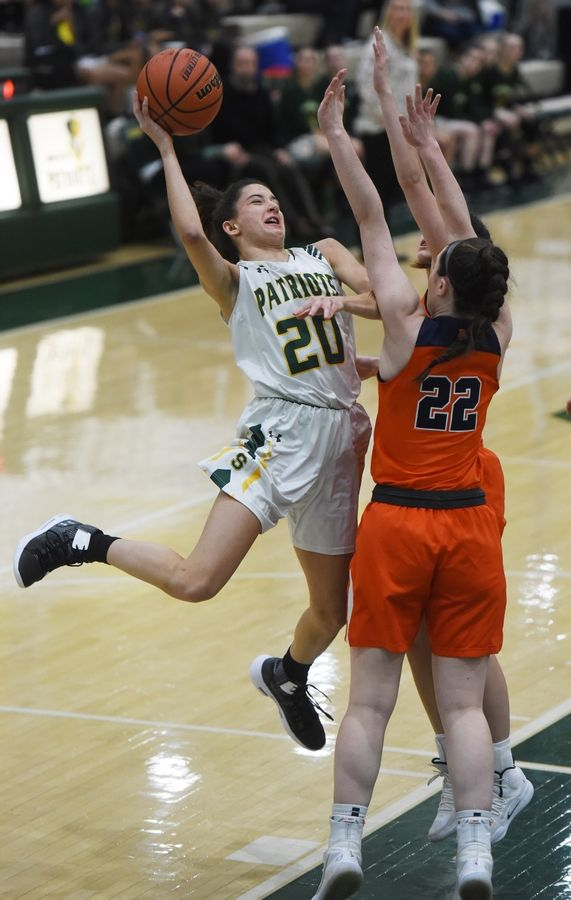 Stevenson's Avery King, left, drives to the basket against Buffalo Grove's defense including Kendra Lee (22) during Saturday's game in Lincolnshire.