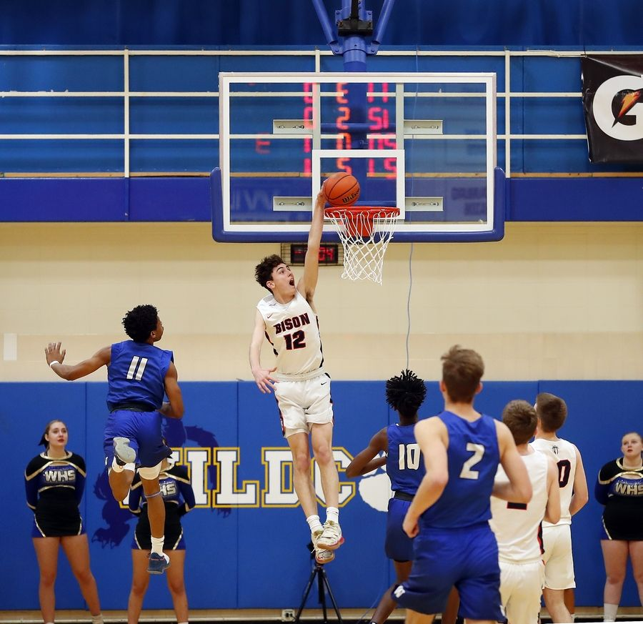Buffalo Grove's Kam Craft (12) throws down a dunk on a breakaway as Wheeling guard Solomon Hudson (11) tries to catch him during basketball Friday at Wheeling High School.