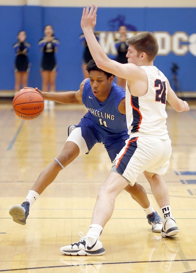 Wheeling guard Solomon Hudson (11) drives past Buffalo Grove's Tyler Kipley (20) during basketball Friday at Wheeling High School.