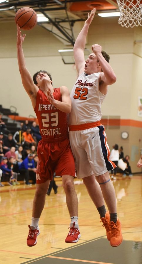 Naperville Central's Kyle Baskin draws contact from Oswego's Connor McCance during Saturday's game in DeKalb.