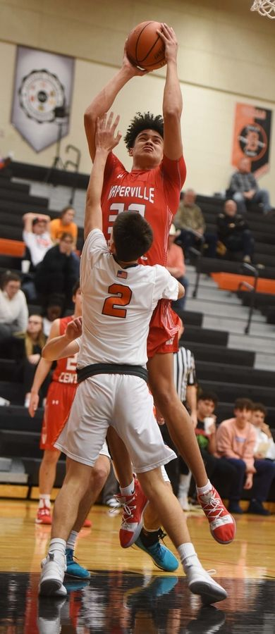 Naperville Central's Chris Conway hits a shot as Oswego's Kevin Jurkovic defends during Saturday's game in DeKalb.