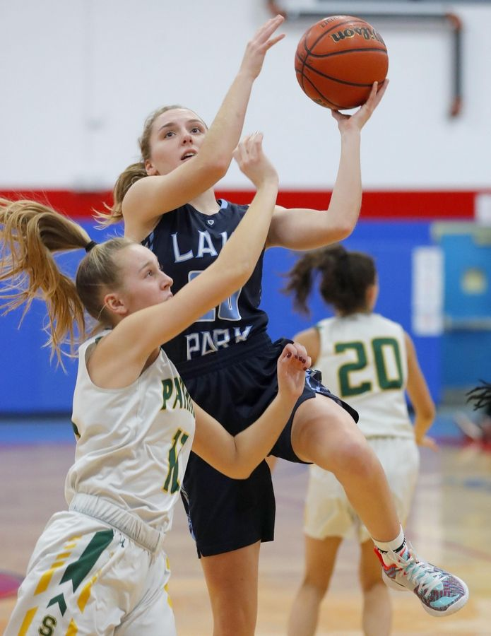 Lake Park's Emma Thorne heads to the hoop past Stevenson's Nikki Kolz in the third place game of the Komaromy Holiday Classic at Dundee-Crown High School in Carpentersville Monday.