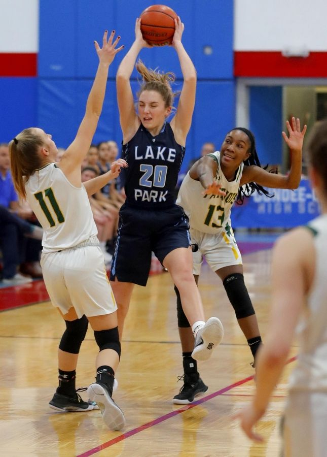 Stevenson's Nikki Kolz, left, and Simone Sawyer, right, guard Lake Park's Emma Thorne in the third place game of the Komaromy Holiday Classic at Dundee-Crown High School in Carpentersville Monday.