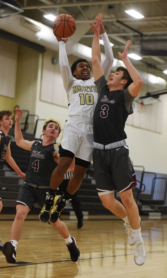 Grayslake North's Jamon Thomas draws contact from Prairie Ridge's Connor Lydon on his way to the basket during Saturday's game in Grayslake. Trailing on the play is Mason Loucks of Prairie Ridge.