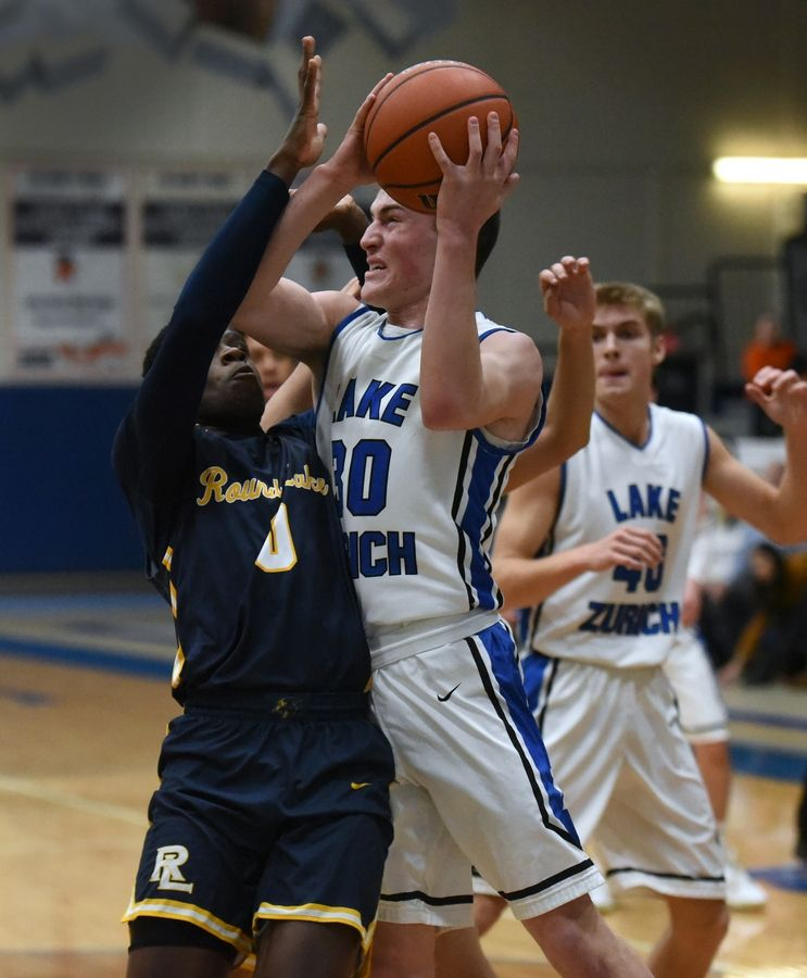 Lake Zurich's Will Tucker (30) goes for a shot while pressured by Round Lake's Nick Pierre during Tuesday's boys basketball game in Lake Zurich.