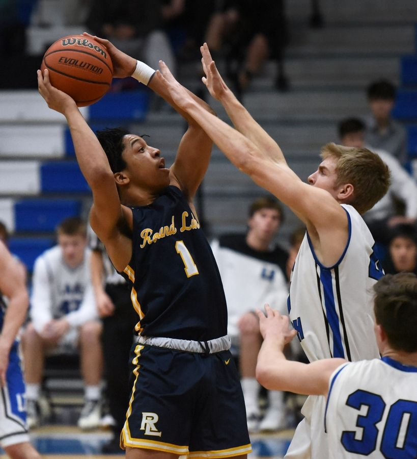 Round Lake's Deveauntay Mcneal (1) takes a shot under pressure from Lake Zurich's Evan Bajerski during Tuesday's boys basketball game in Lake Zurich.