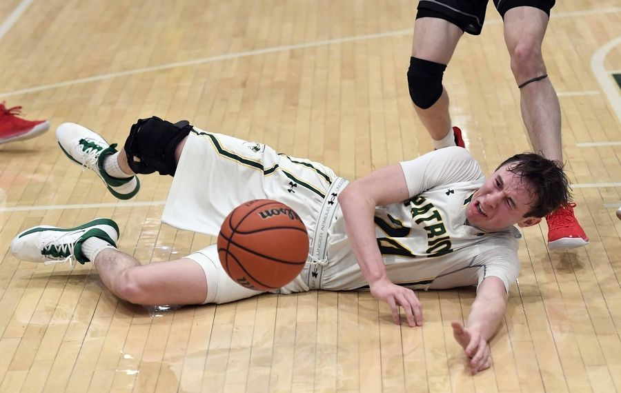 Stevenson's Matthew Ambrose hits the floor as he slips under pressure from Mundelein's Conor Enright in the first half of varsity basketball at Stevenson on Friday.