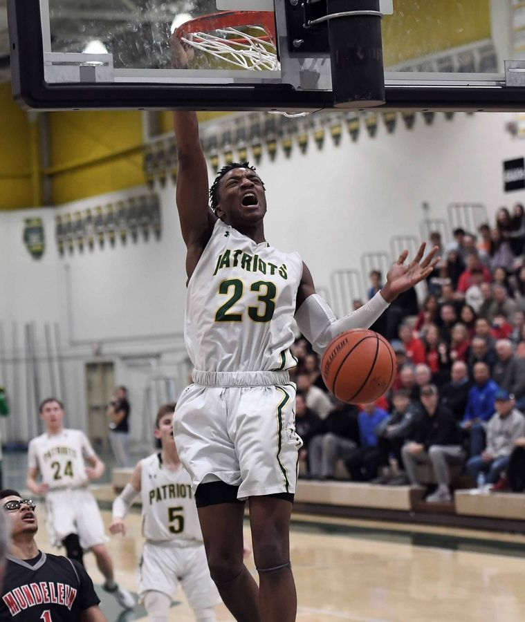 Stevenson's Robert Holmes slams one home that was set up by a pass from teammate Evan Ambrose in the first half of varsity basketball at Stevenson on Friday.