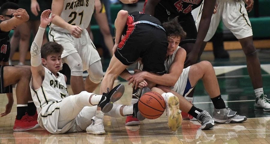 Stevenson's Jacob Tenner gets wrapped up in a scramble for the ball with teammate Evan Ambrose in the first half of varsity basketball at Stevenson on Friday.