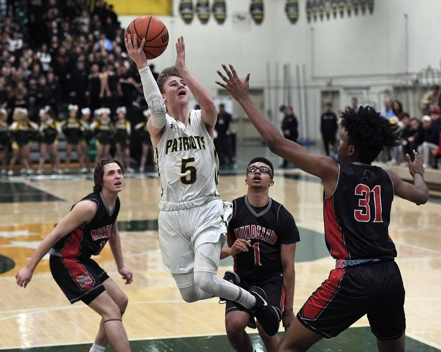 Stevenson's Evan Ambrose is poetry in motion as he eyes the basket despite pressure from the Mundelein defense in the first half of varsity basketball at Stevenson on Friday.