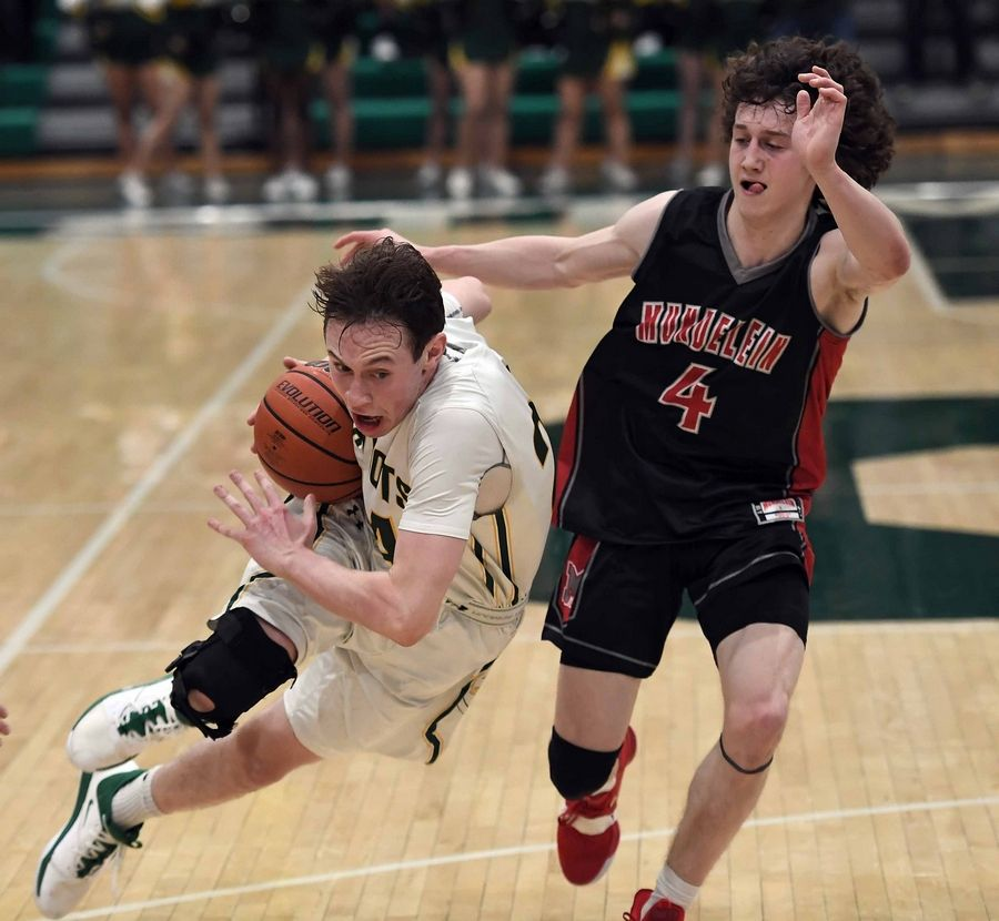 Stevenson's Matthew Ambrose eyes the floor as Mundelein's Conor Enright applies pressure in the first half of varsity basketball at Stevenson on Friday.
